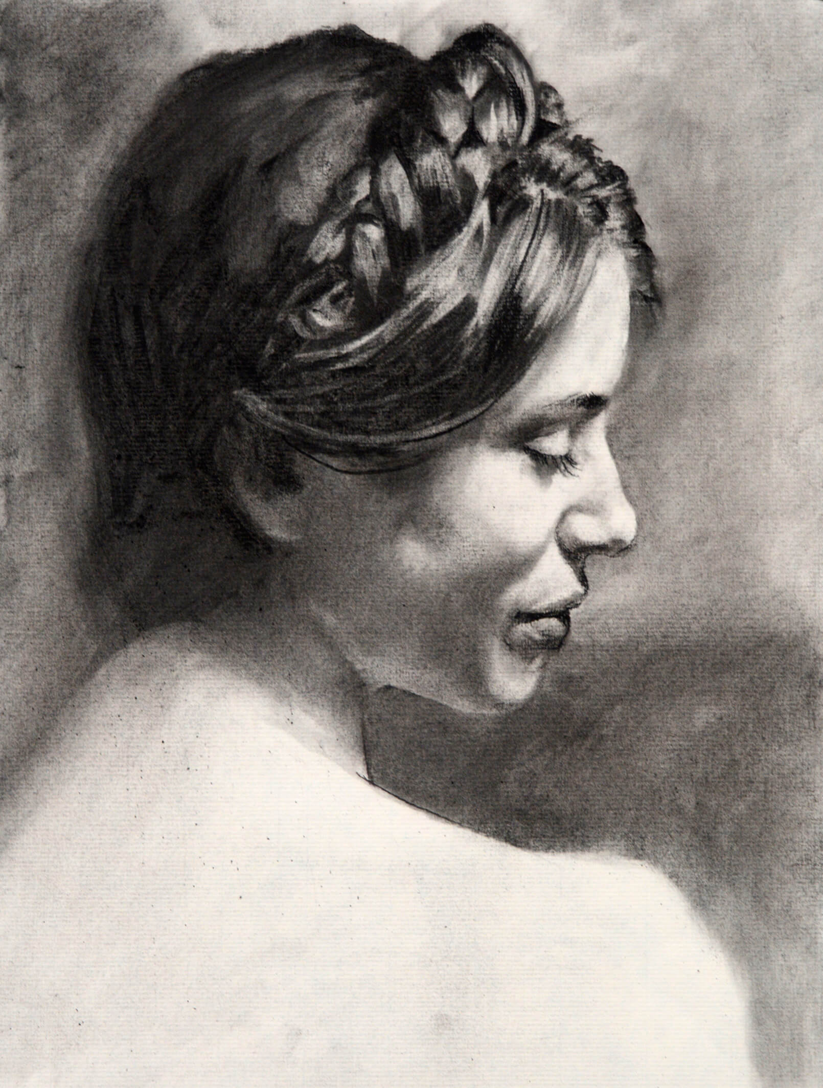 Realistic charcoal portrait of a woman with a top braid in profile with a downward gaze
