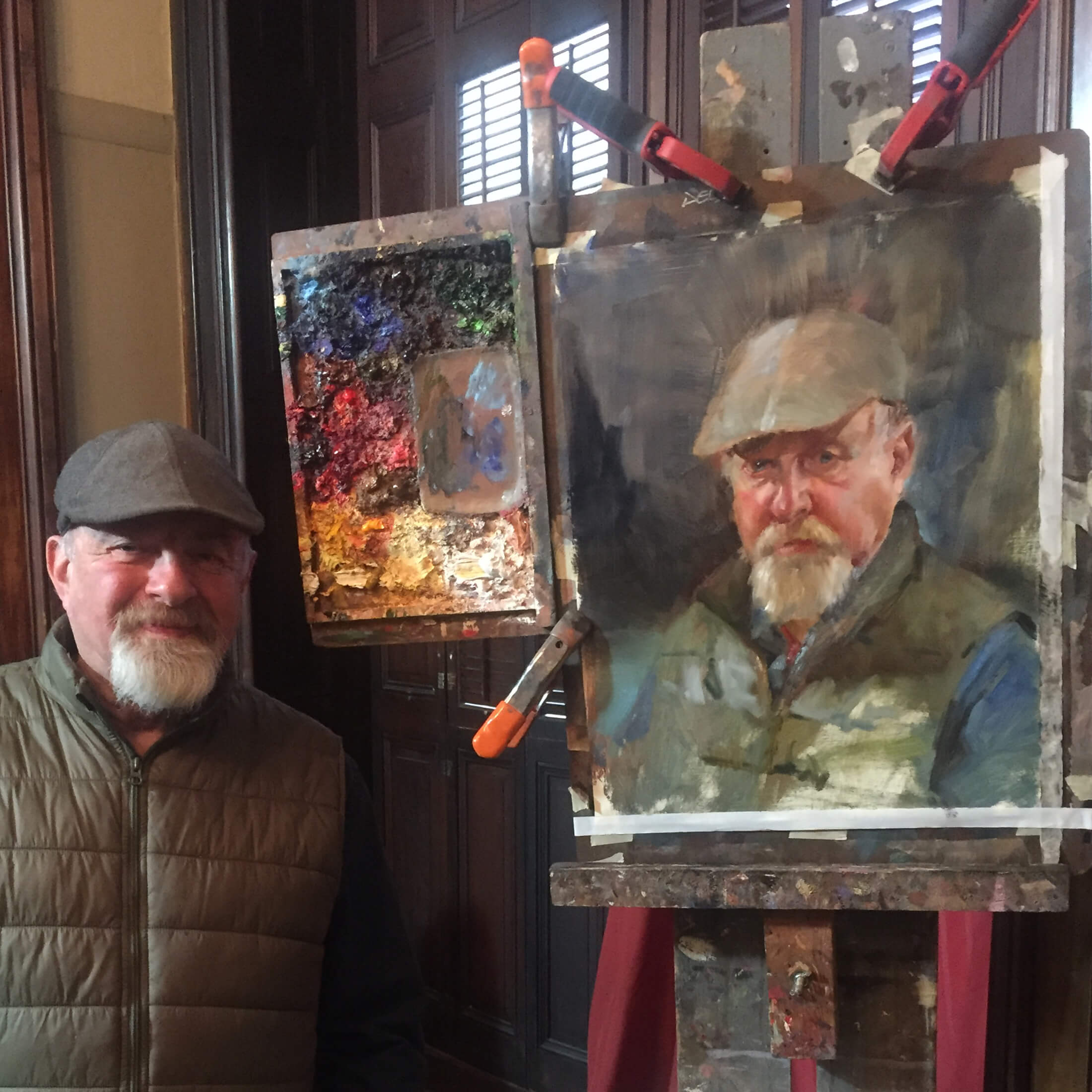 Portrait subject standing next to the portrait painted by artist Lenin Delsol