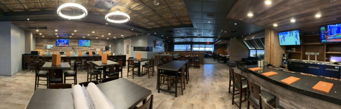 Sushi restaurant with black tables, TV's mounted on wall, and circle lighting fixtures