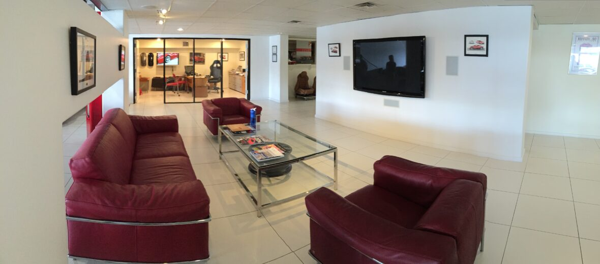 Waiting Area with red couches, glass table and mounted tv on opposite white walls