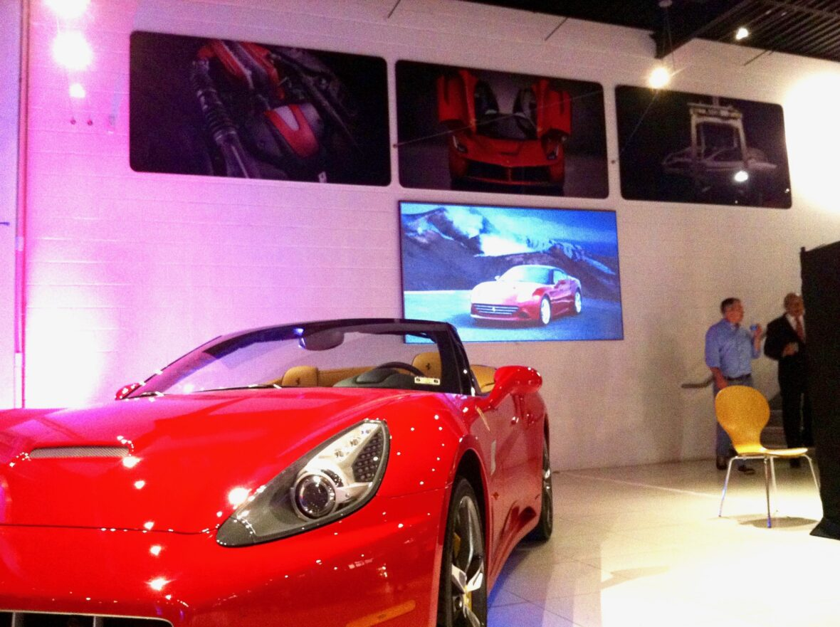 Commercial TV Installations on same wall behind high-end red dealership car