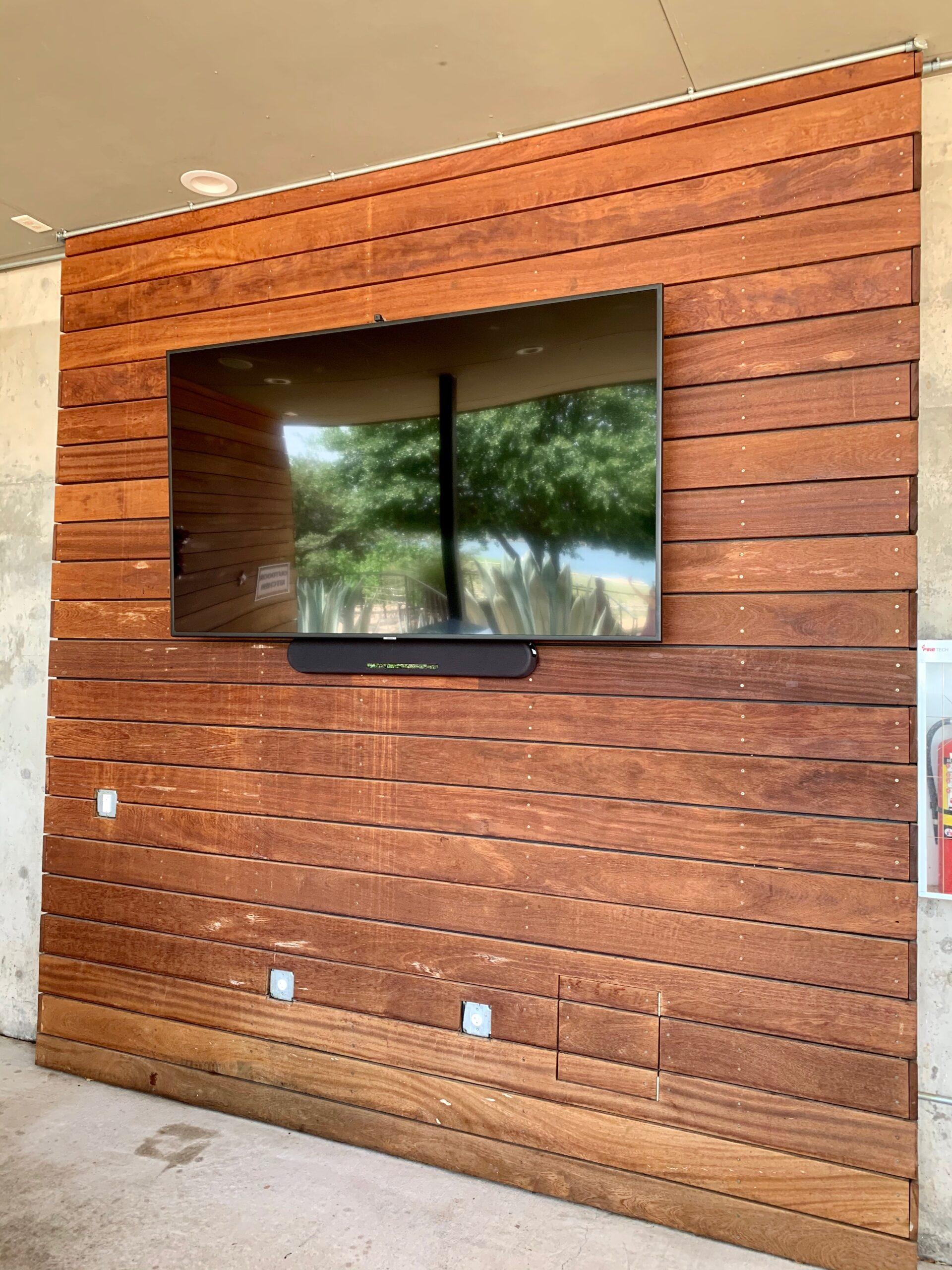 Outdoor TV mounted weatherproof TV installed on wood.