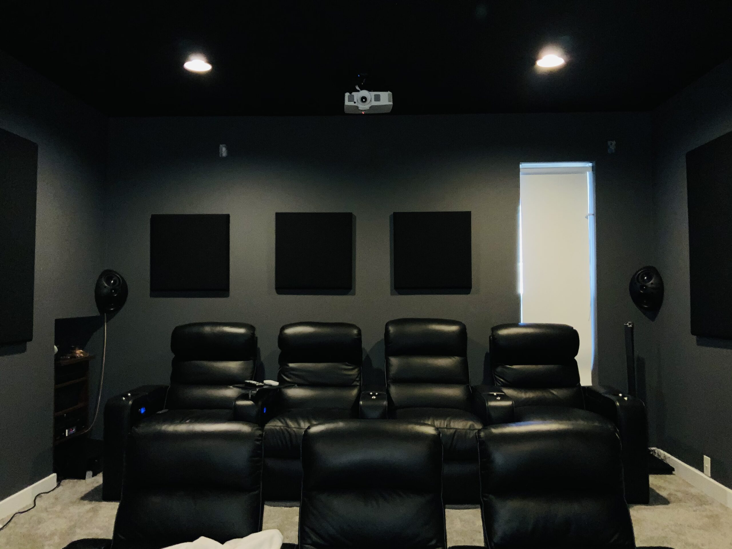 Dedicated home theater room demo with short throw laser projection, custom seating and acoustic panels