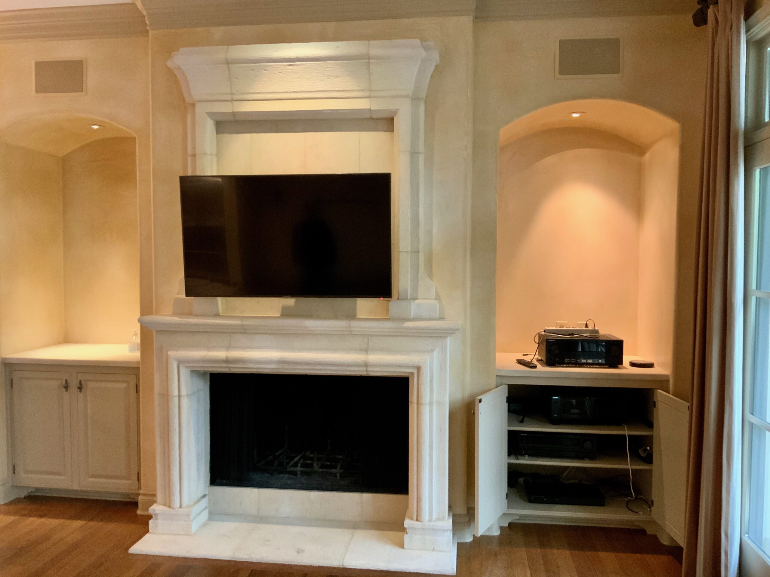 Fireplace TV mounted above with integrated surround sound system