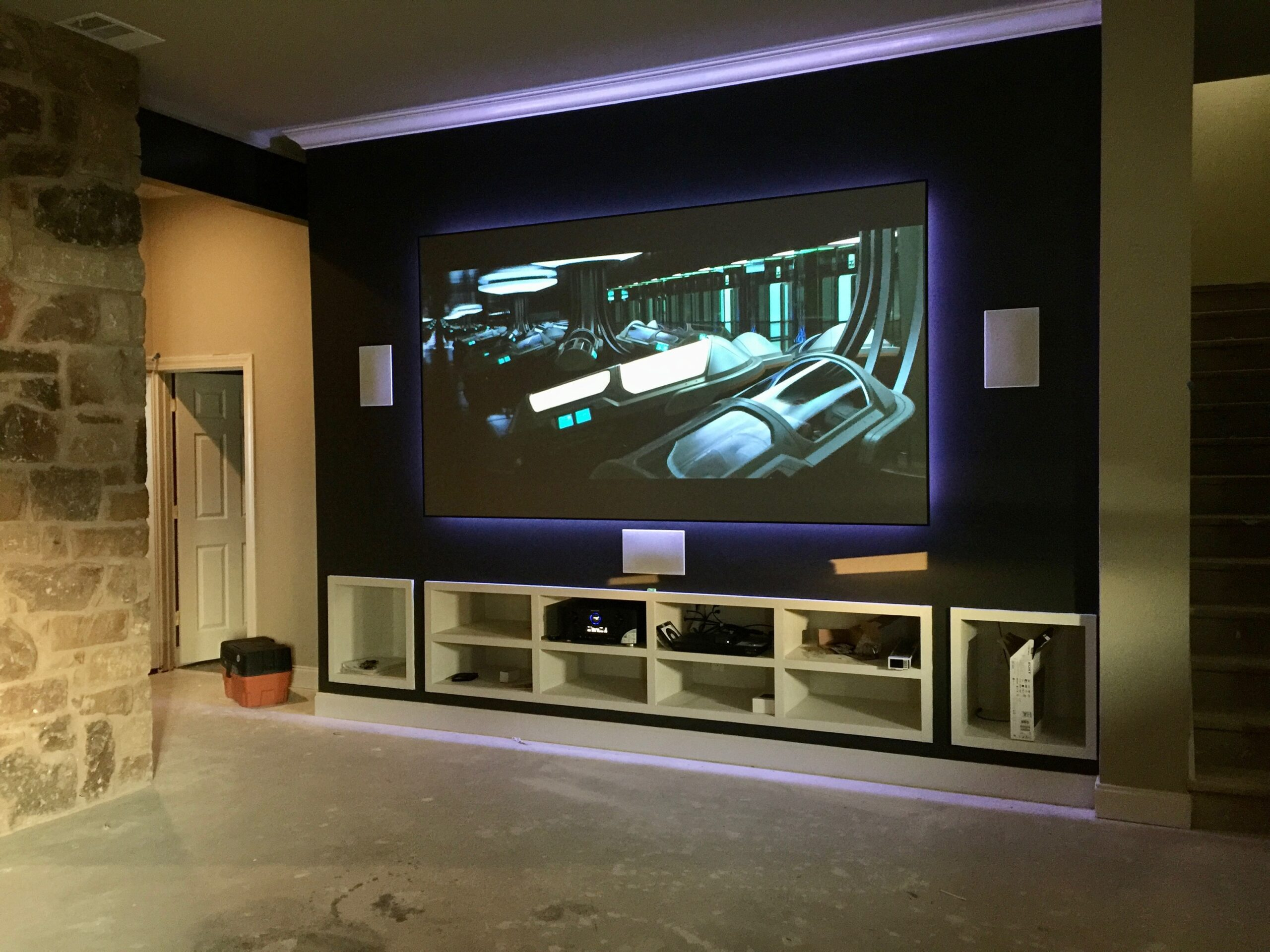 Home theater room with short throw laser projection, hidden pristine sound system and custom theater lighting