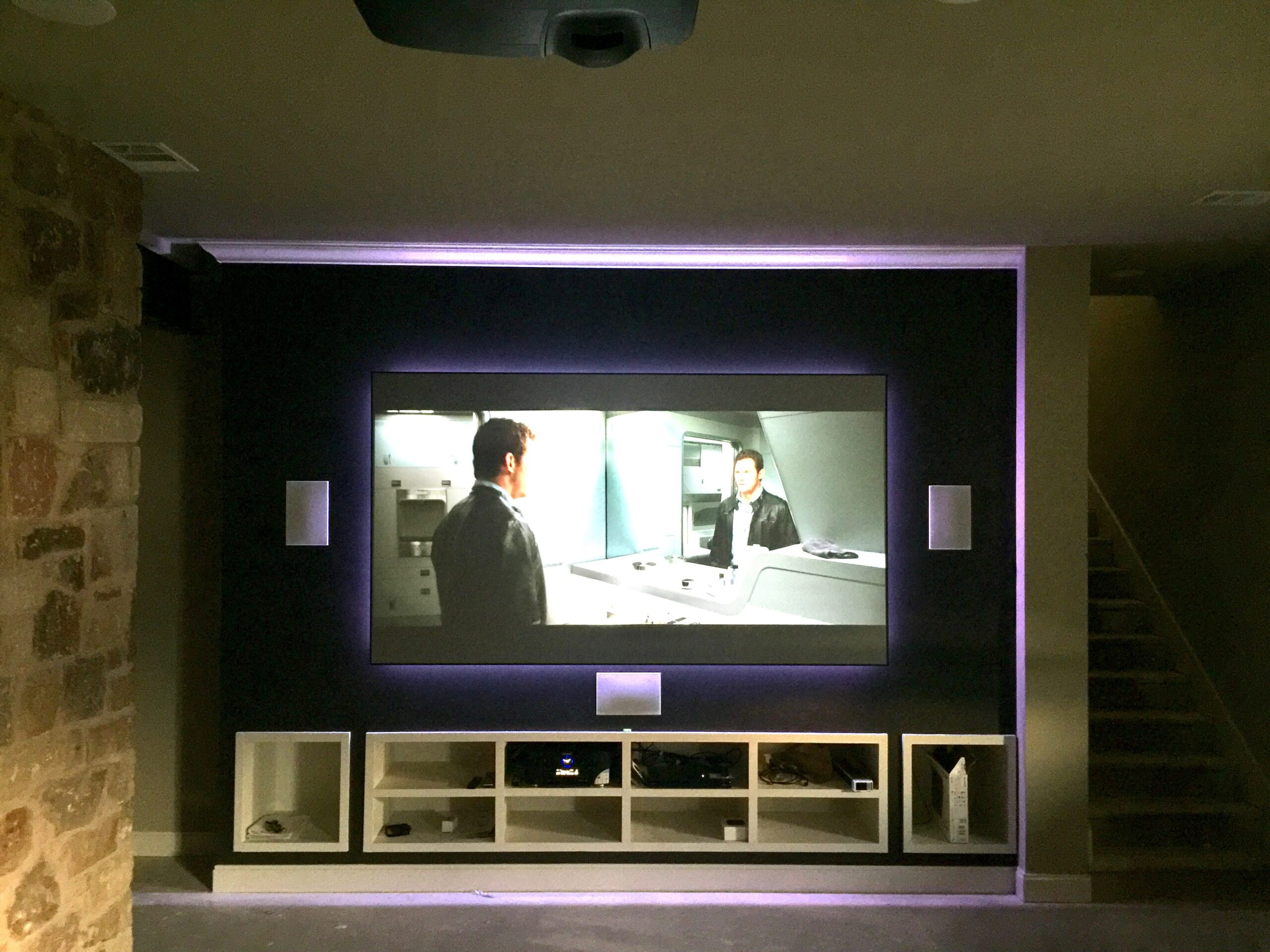 Home theater room with short throw laser projection, hidden pristine sound system and interior theater lighting