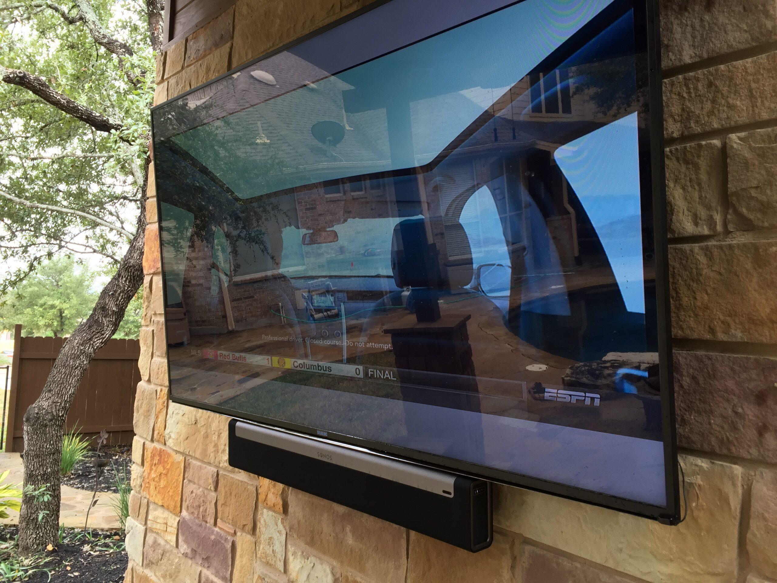 Outdoor weatherproof TV mounted on brick wall