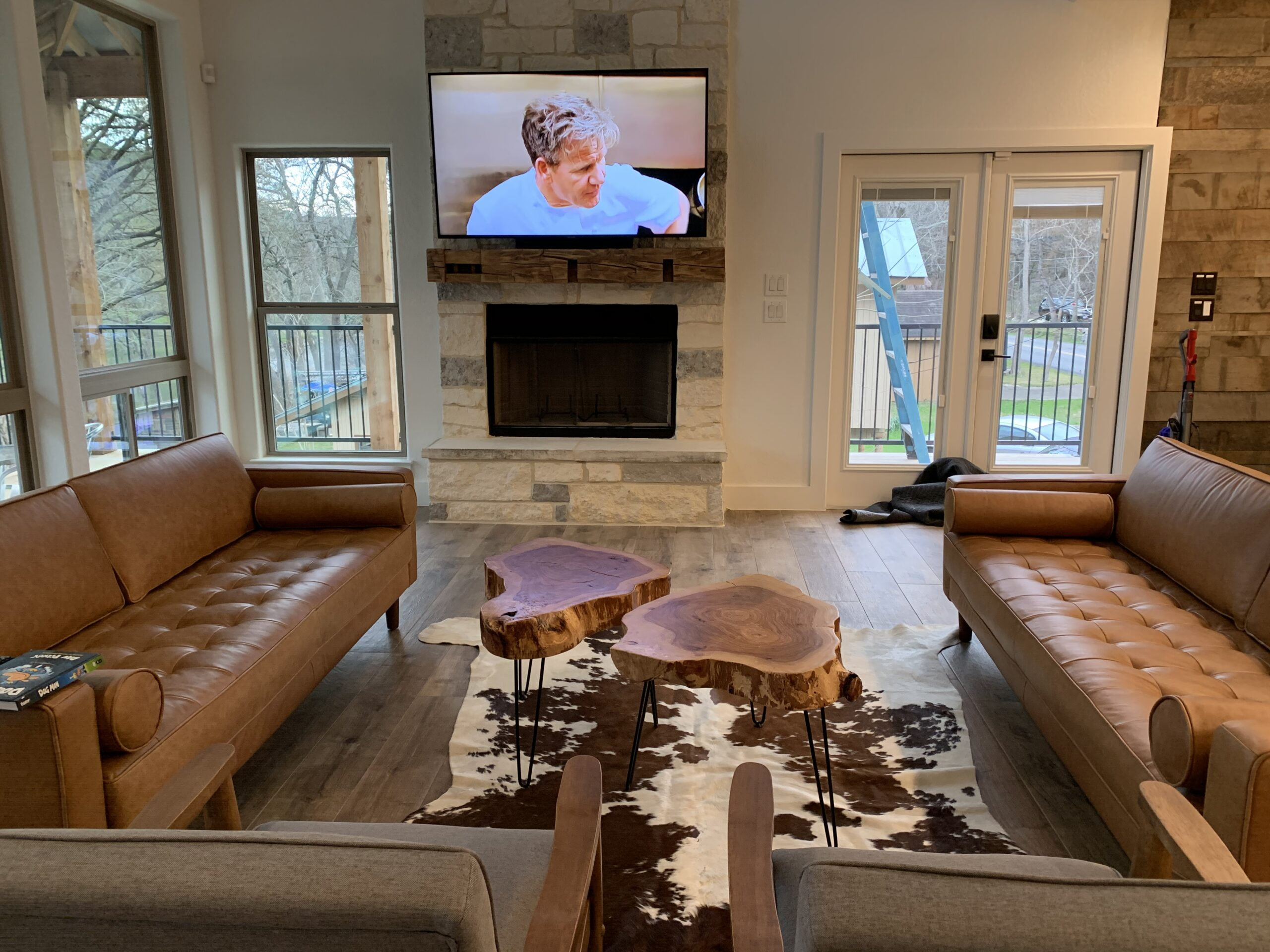 Smart system integrated media room with tv mounted above fireplace