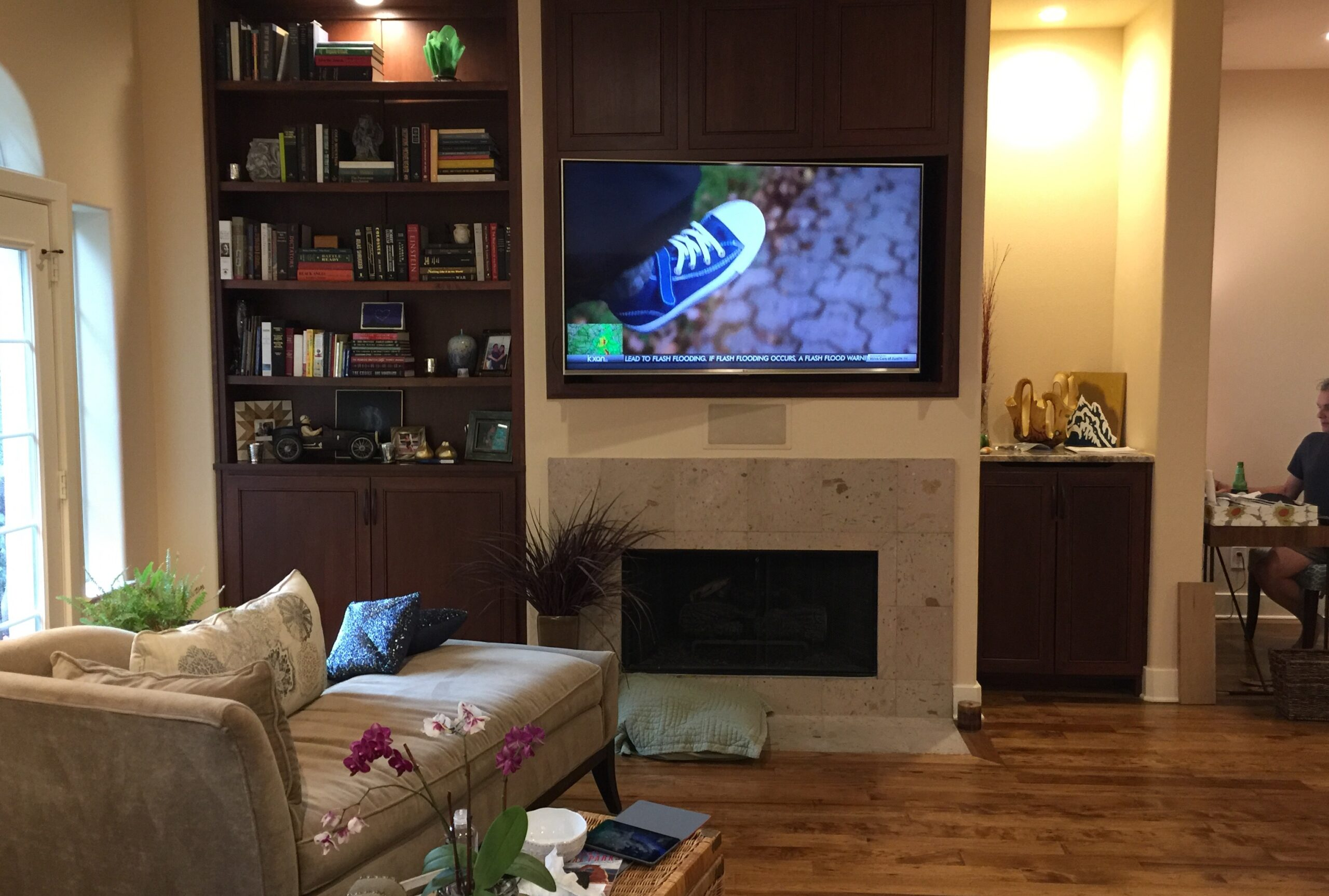 Media room with hidden speakers and TV installed in wall above fireplace