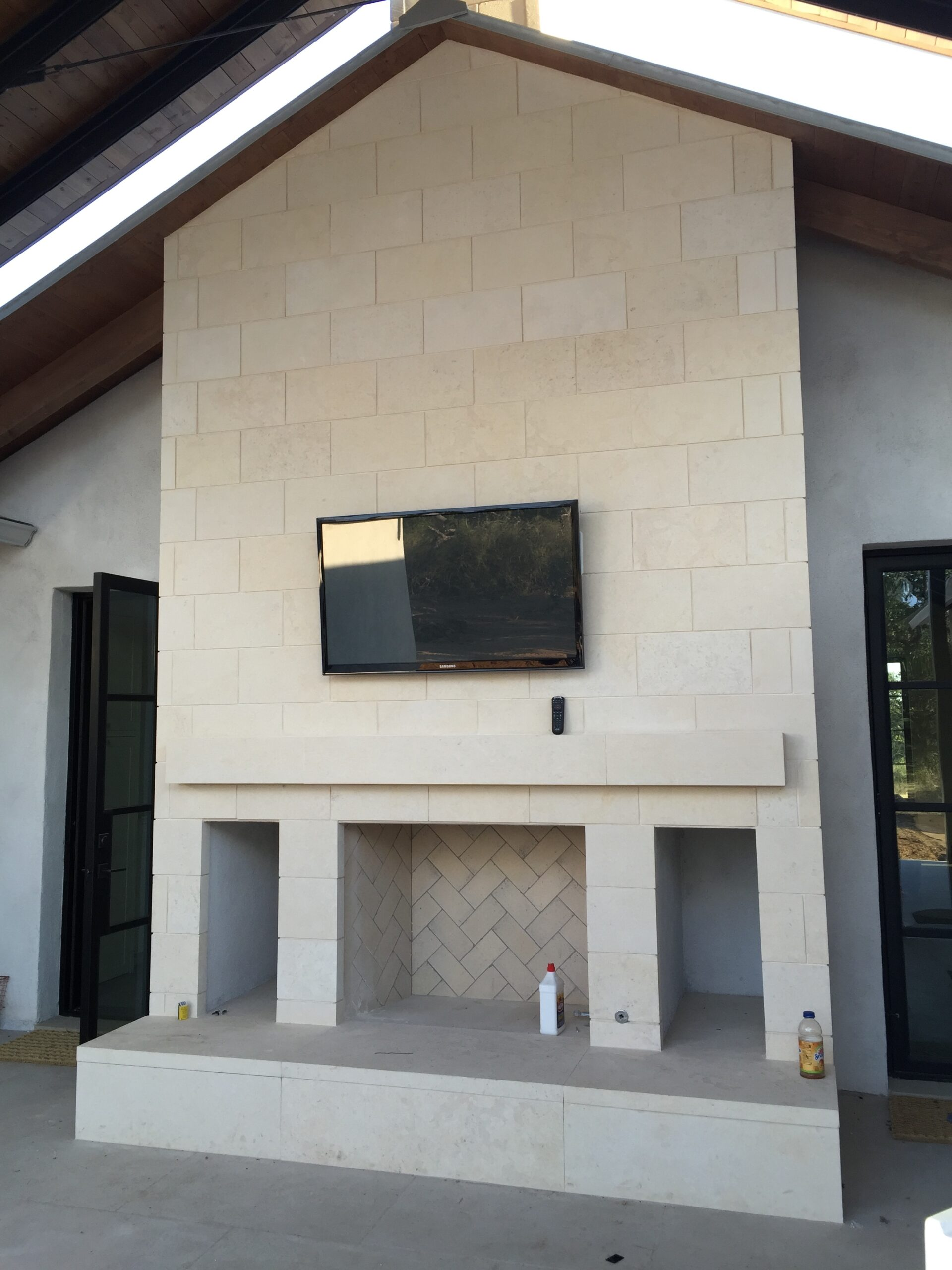 Outdoor TV installed above fireplace