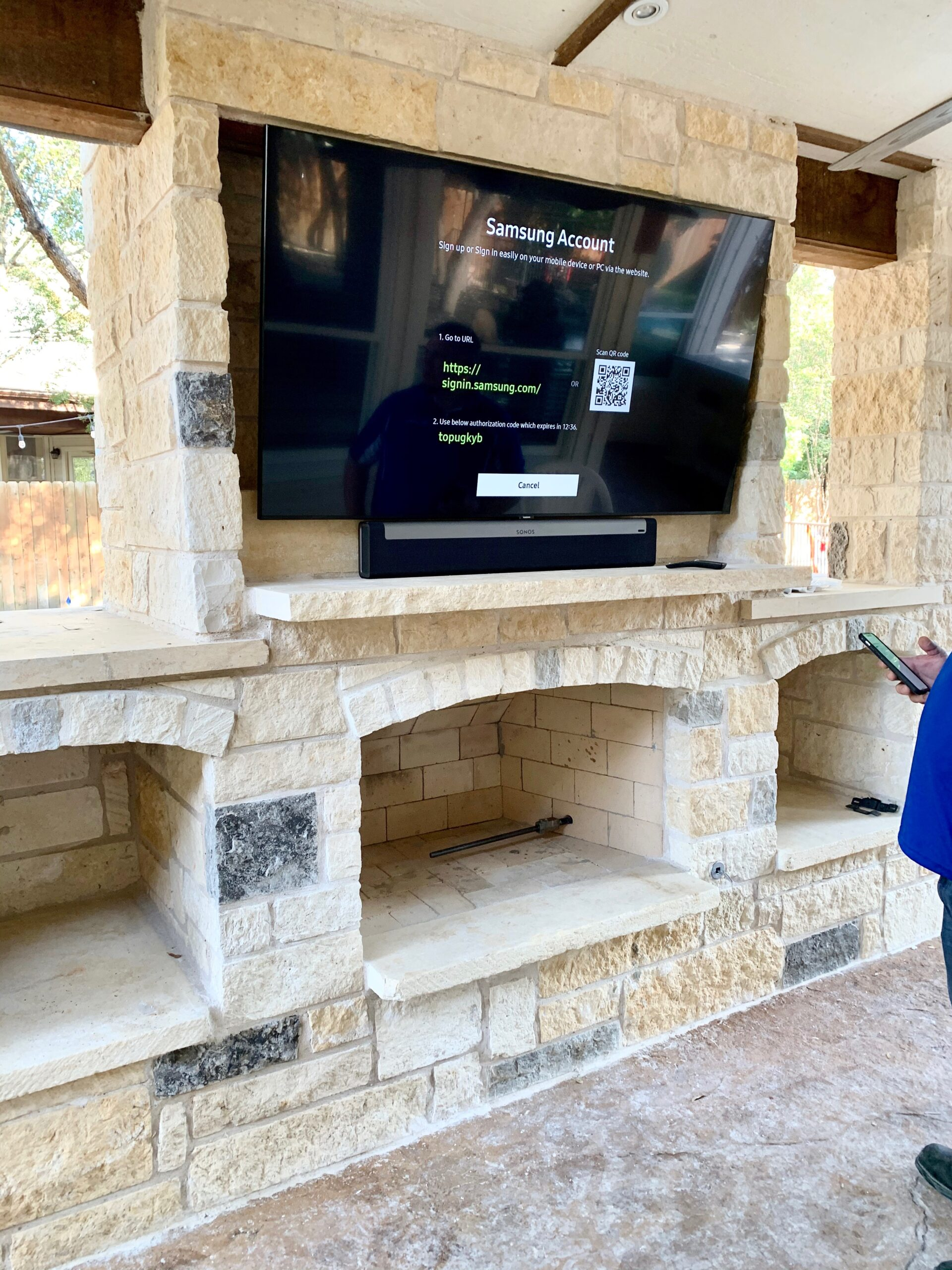 Outdoor weatherproof TV installed above fireplace