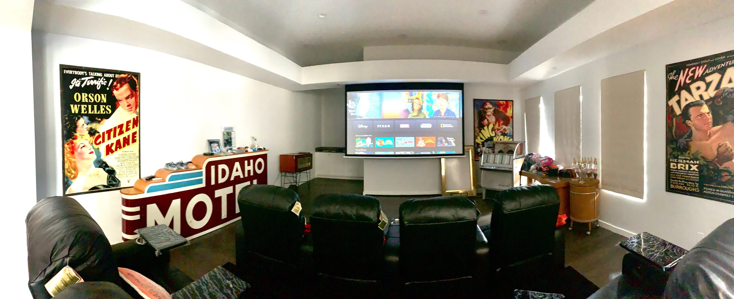 Media room retractable screen, custom leather theater seating and motorized shades