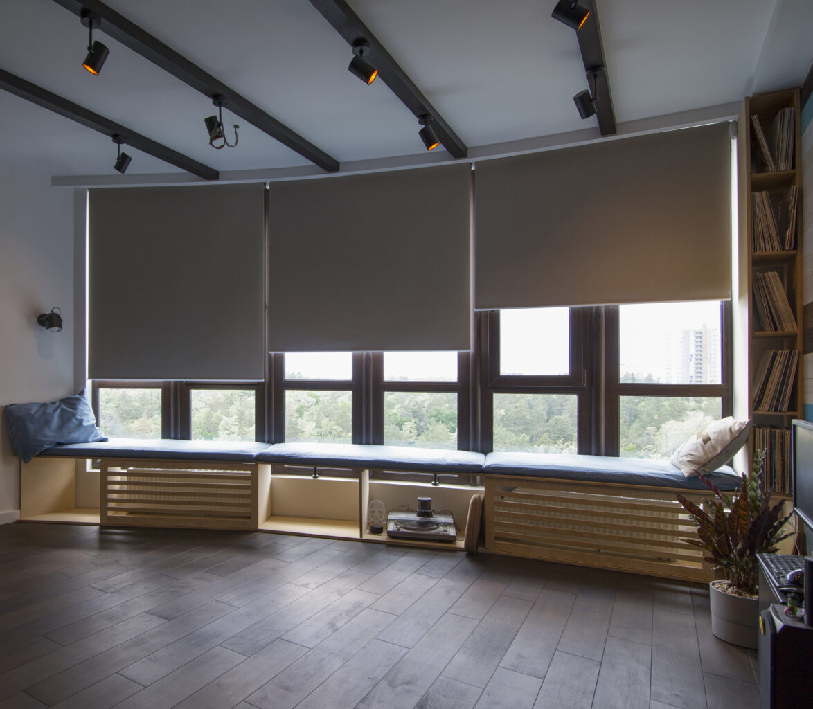 the interior. Automatic roller blinds beige color on big glass windows. Remote Control Shades are above the windosill with pillows. Summer. Green trees outside.