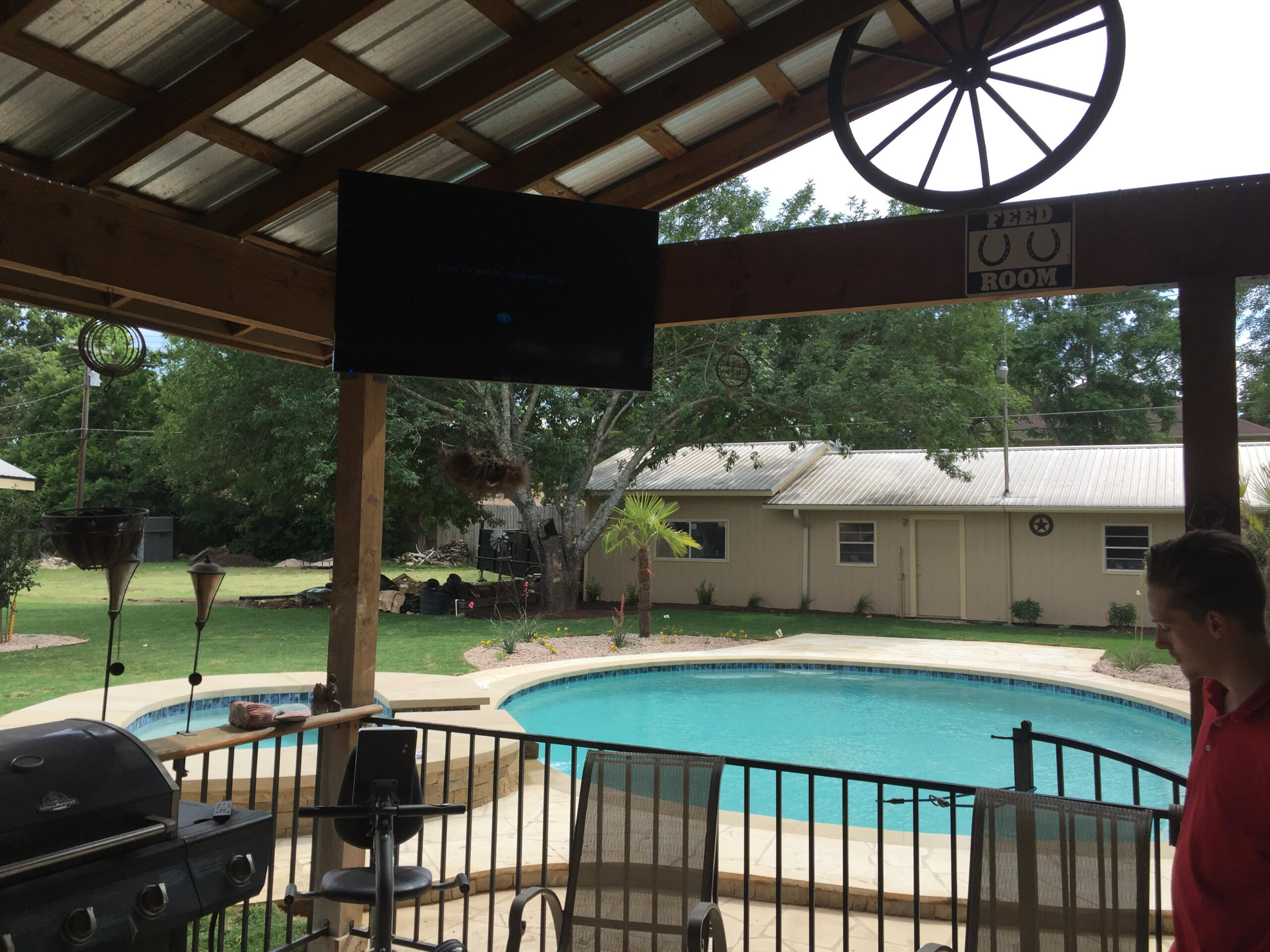 Outdoor space with mounted TV and sound system controlled from smart source