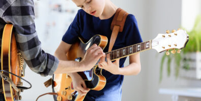 Boy playing electric guitar. Student is learning music from male guitarist. They are in training class at Wilton Music Studios