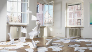 Papers flying and scattered across a room while the three windows are all open.