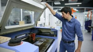 Man opening up lid of 3D printer in a personal protective equipment manufacturer.