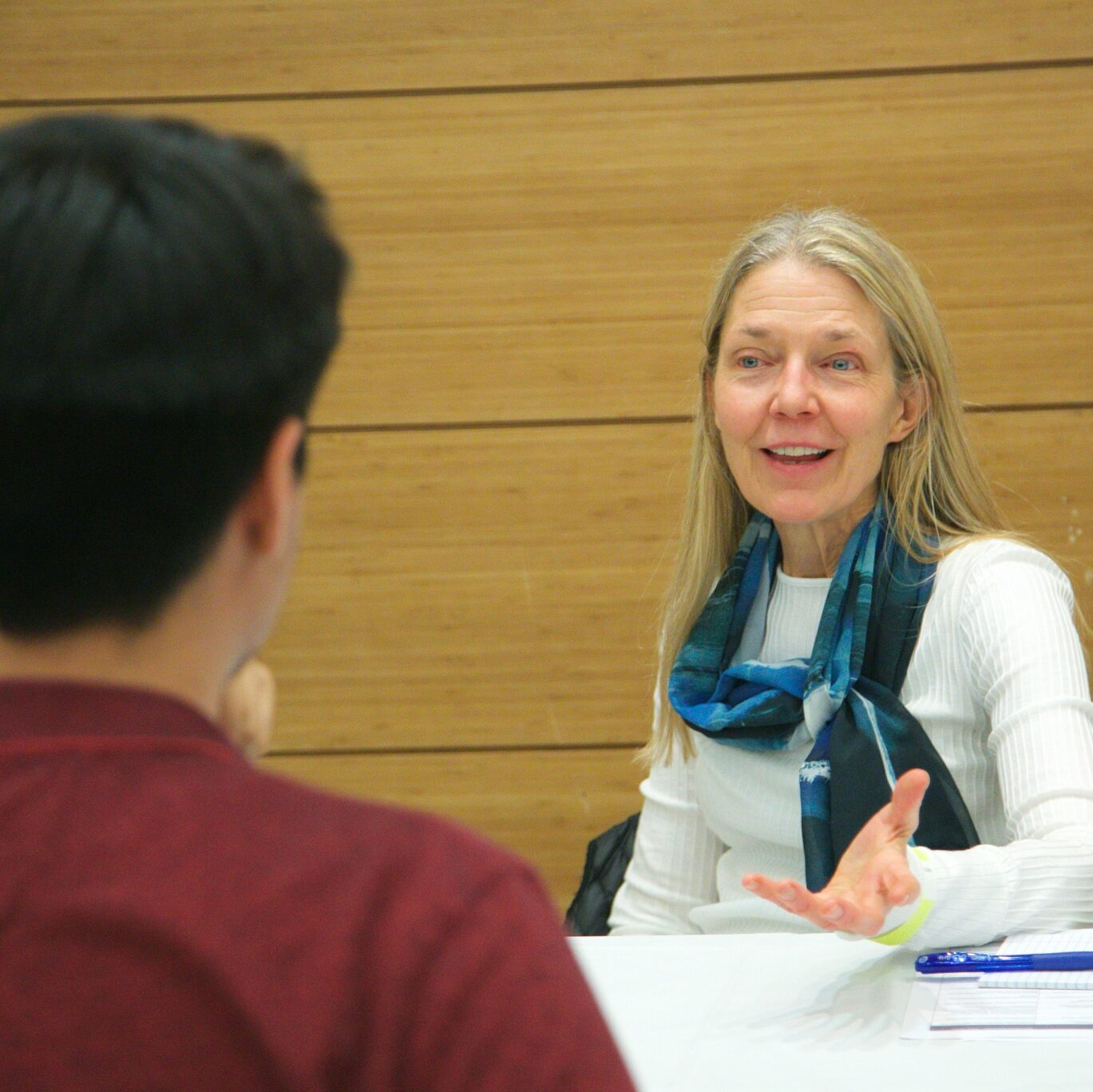 Advisor speaking with a student during a session at a white table