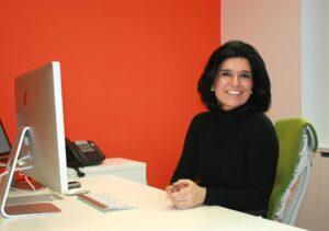 Shabnam Rezaei sitting at a desk smiling at the camera