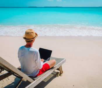 remote work concept -young man working on laptop at beach