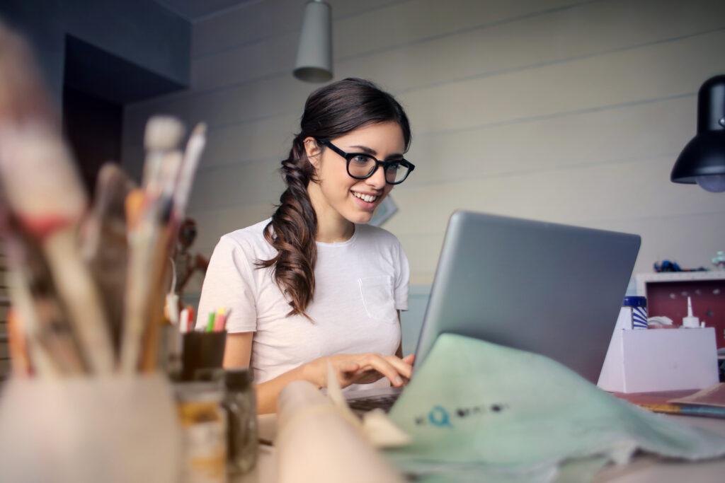 girl with glasses working on a laptop
