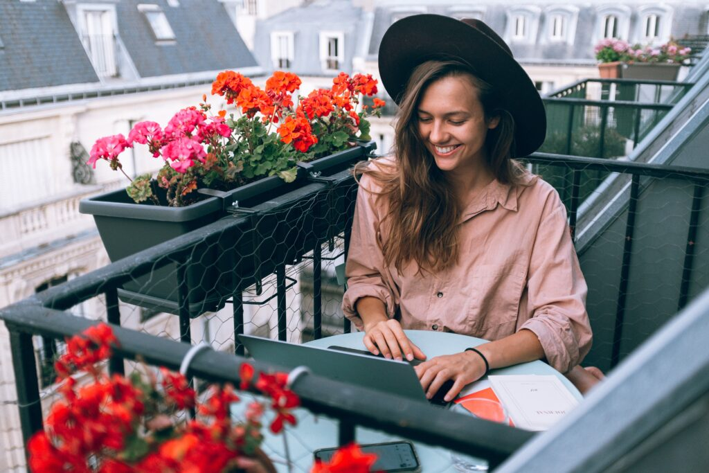 woman smiling and working on the laptop on the balconny