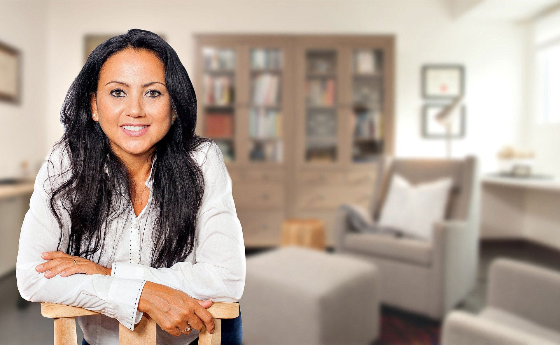 confident woman behind chair in living room