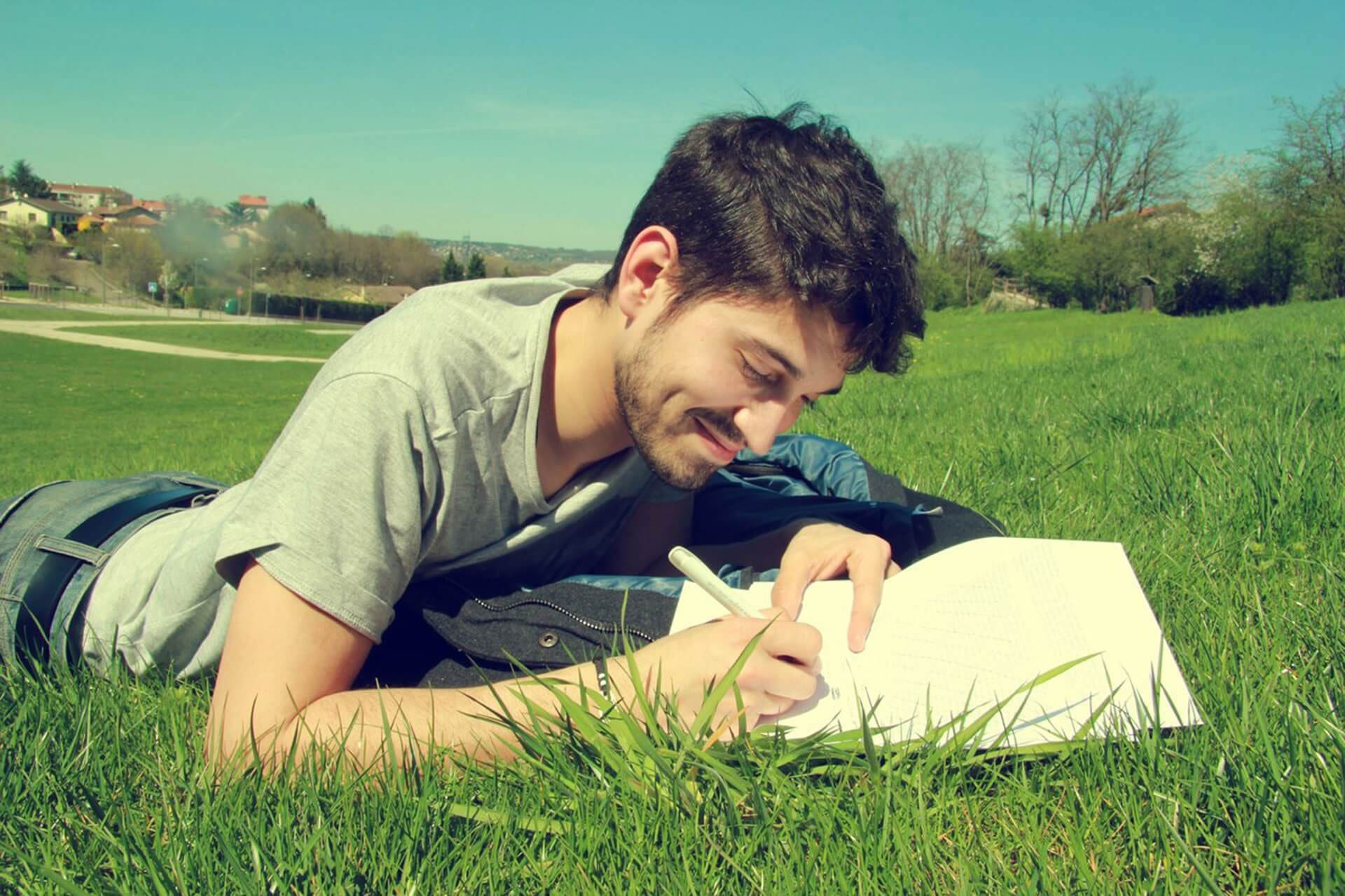 man laying on grass writing in notebook