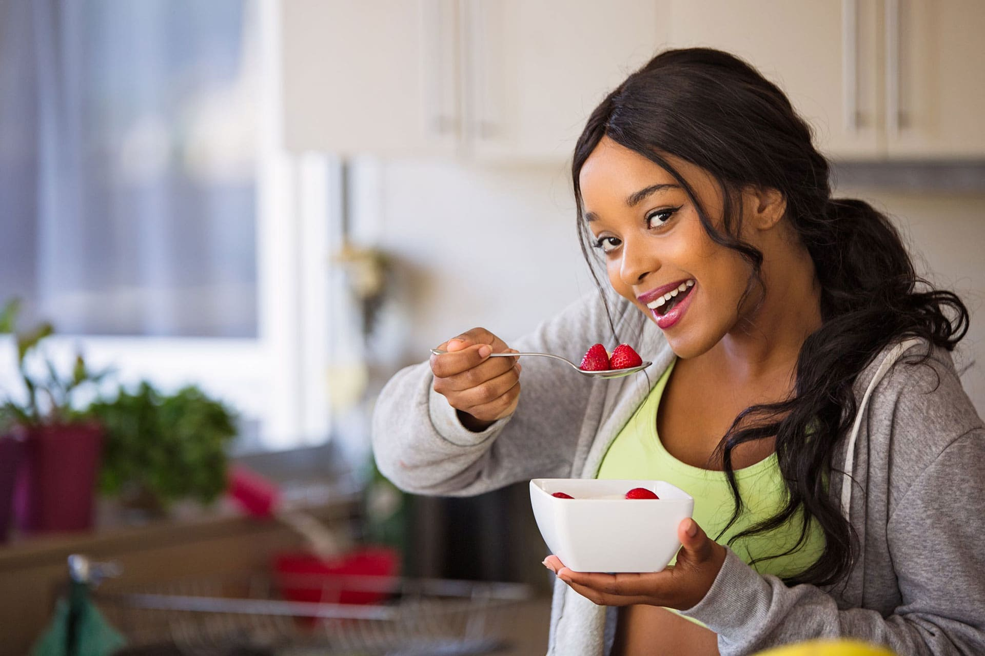 woman eating strawberries out of a bowl