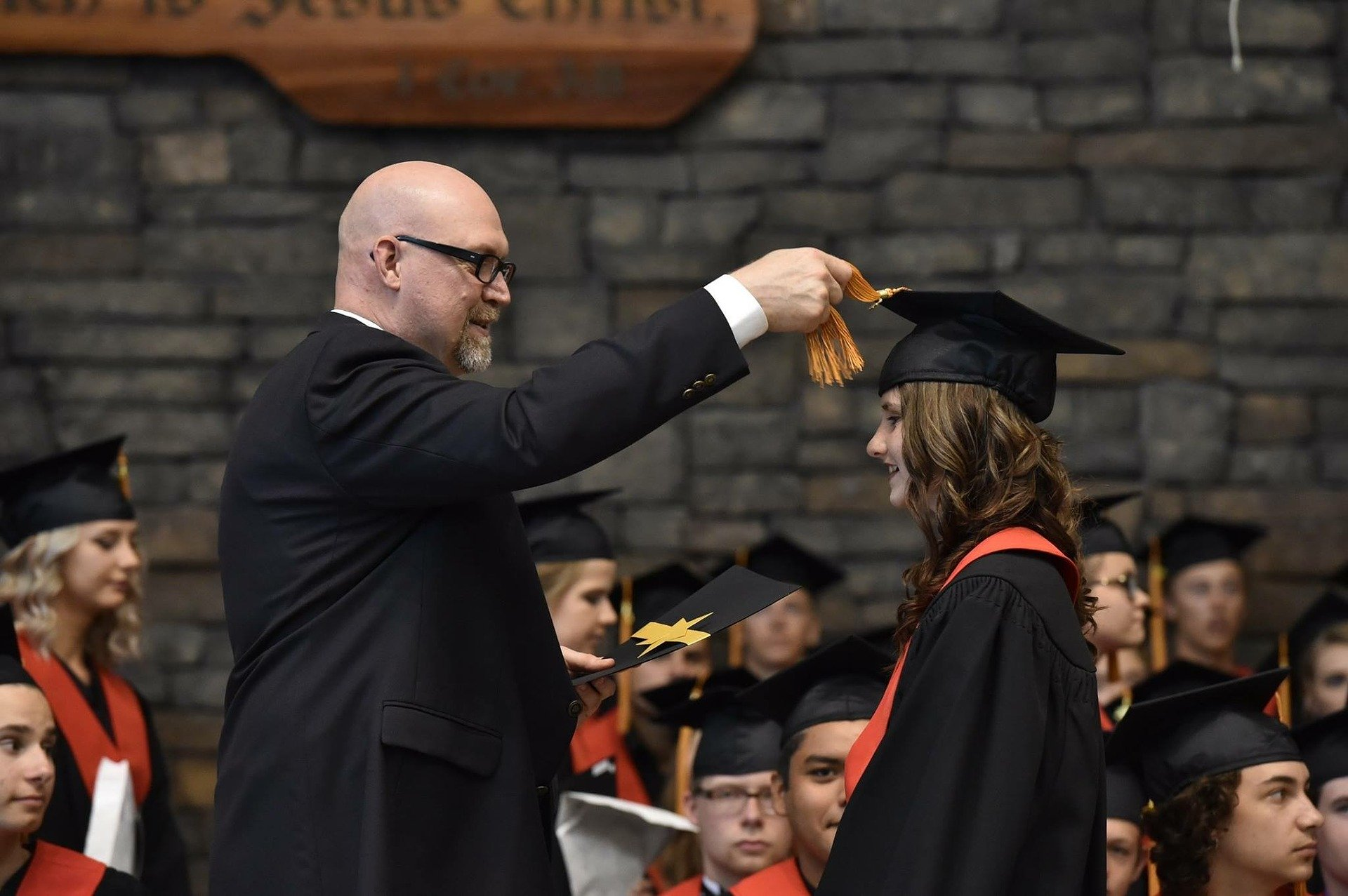 father helping daughter with graduation cap