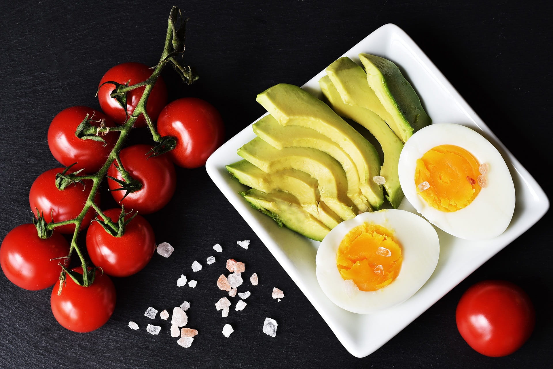 tomato vine and plate of eggs and avocados