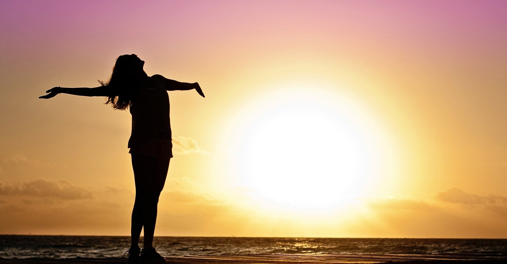 woman at beach at sunset with arms spread