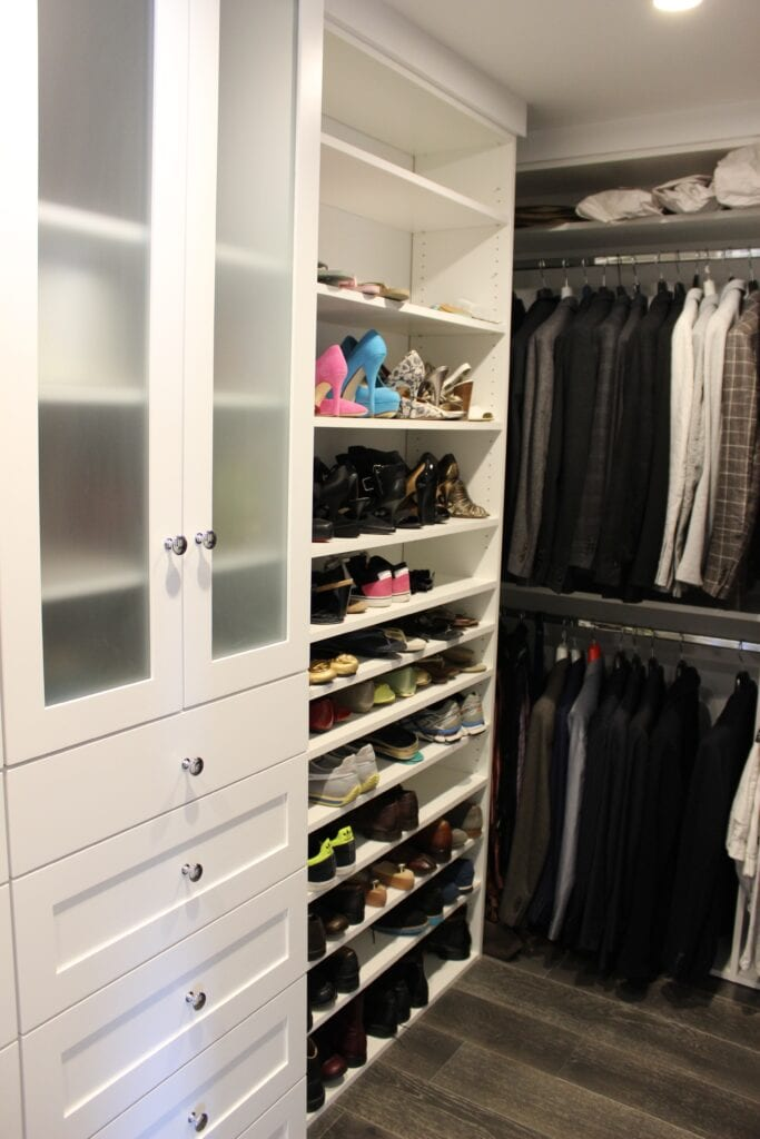 White closet and cabinets with shoes and clothes