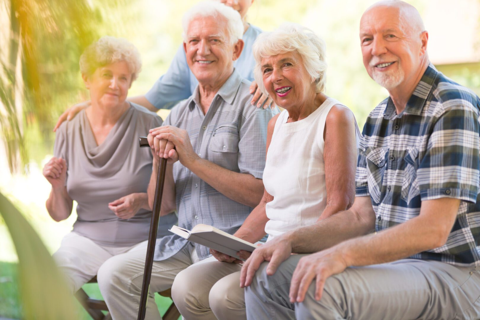 Smiling elderly people spending time together at patio of nursing house