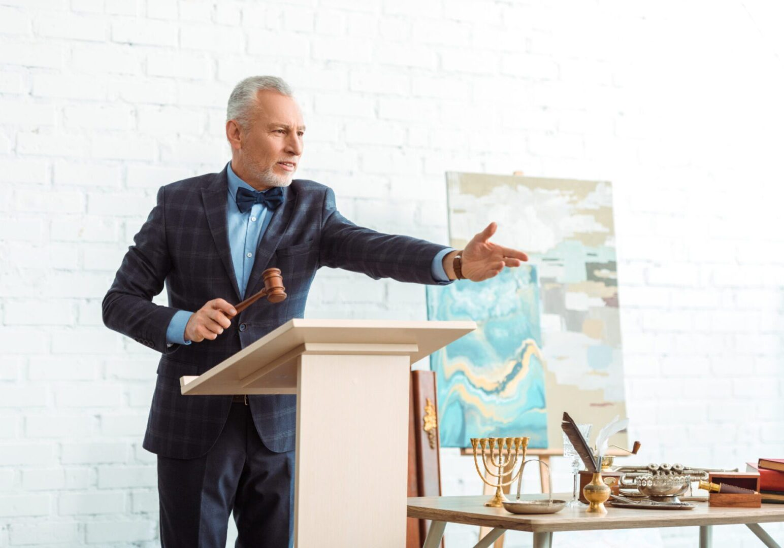 handsome auctioneer holding wooden gavel and pointing with hand during auction