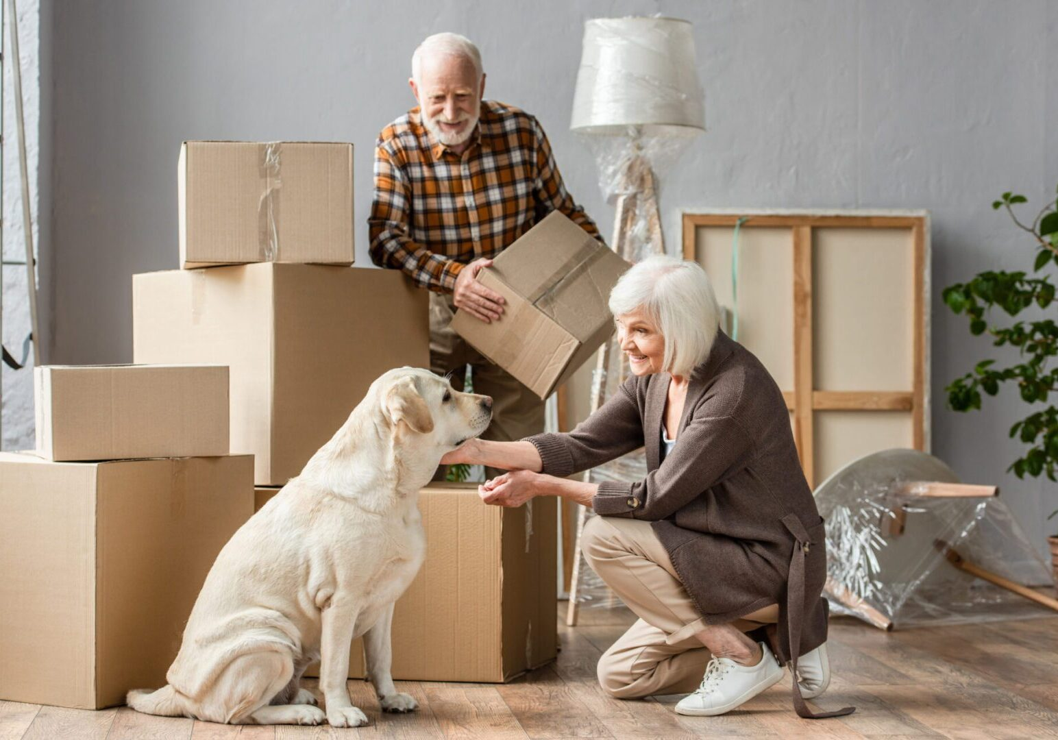 Senior,Woman,Petting,Dog,In,New,House,While,Husband,Holding