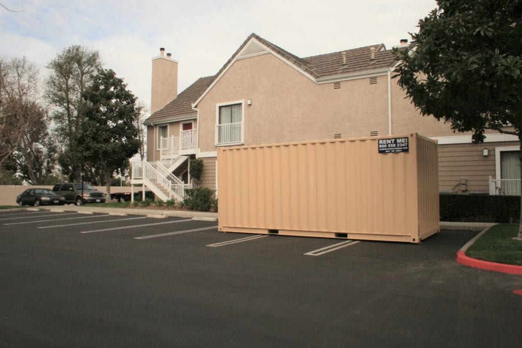 shipping container in parking lot near apartment building