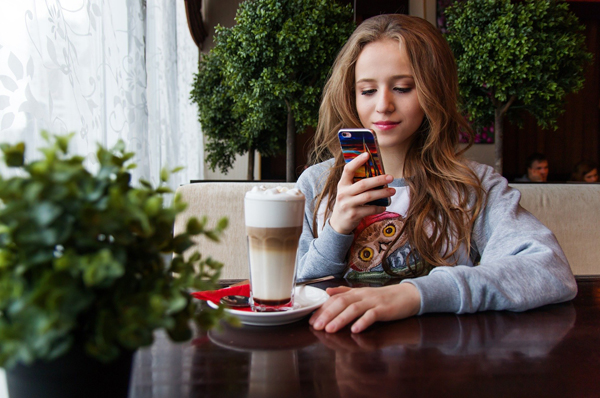 Young woman sitting at a table with coffee looking at her phone
