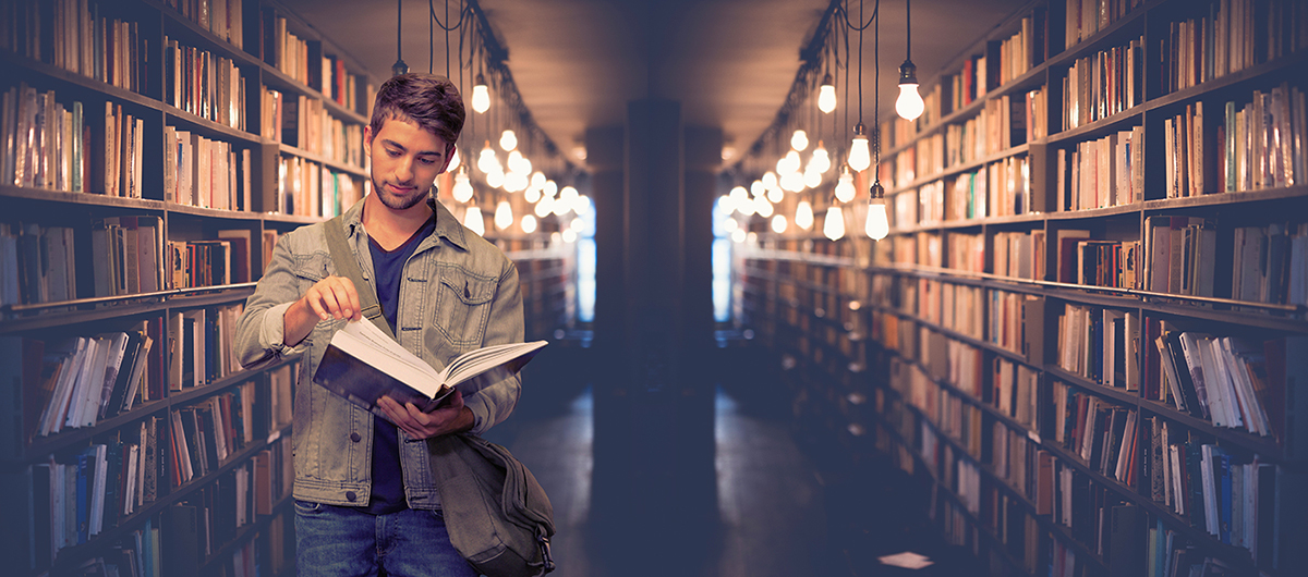 Young man standing in aisle of library flipping through pages of a book