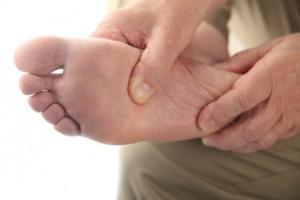 a man checks his aching foot