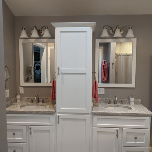 This picture is showing the double vanities now on one wall with the linen cabinet between them.  Prevents the vanities from sticking out into the room and blocking the flow.  White painted vanities with quartz tops are elegant and beautiful as well as functional