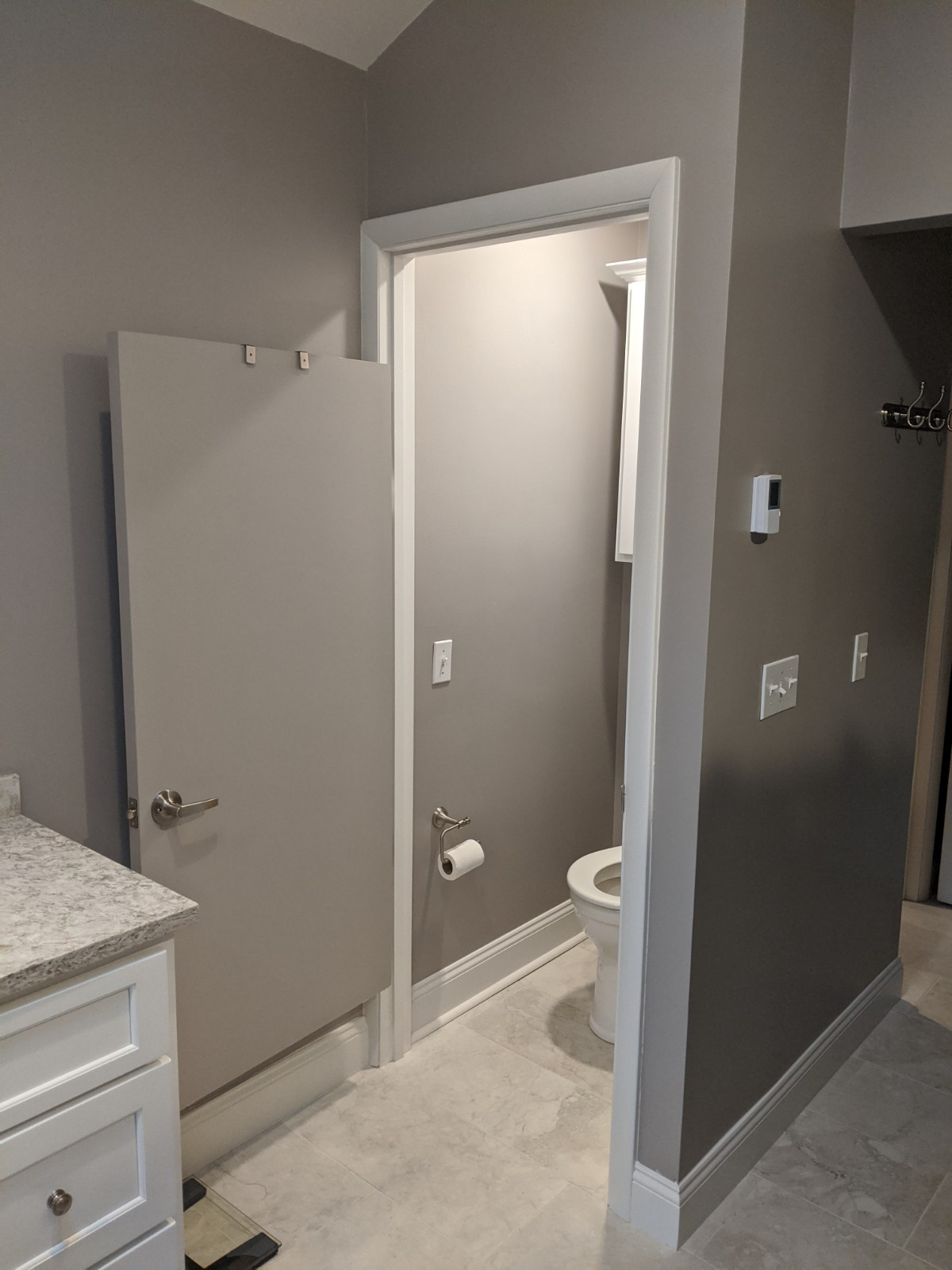 This picture shows the updated tile floor throughout the bathroom as well as the modern door for the water closet