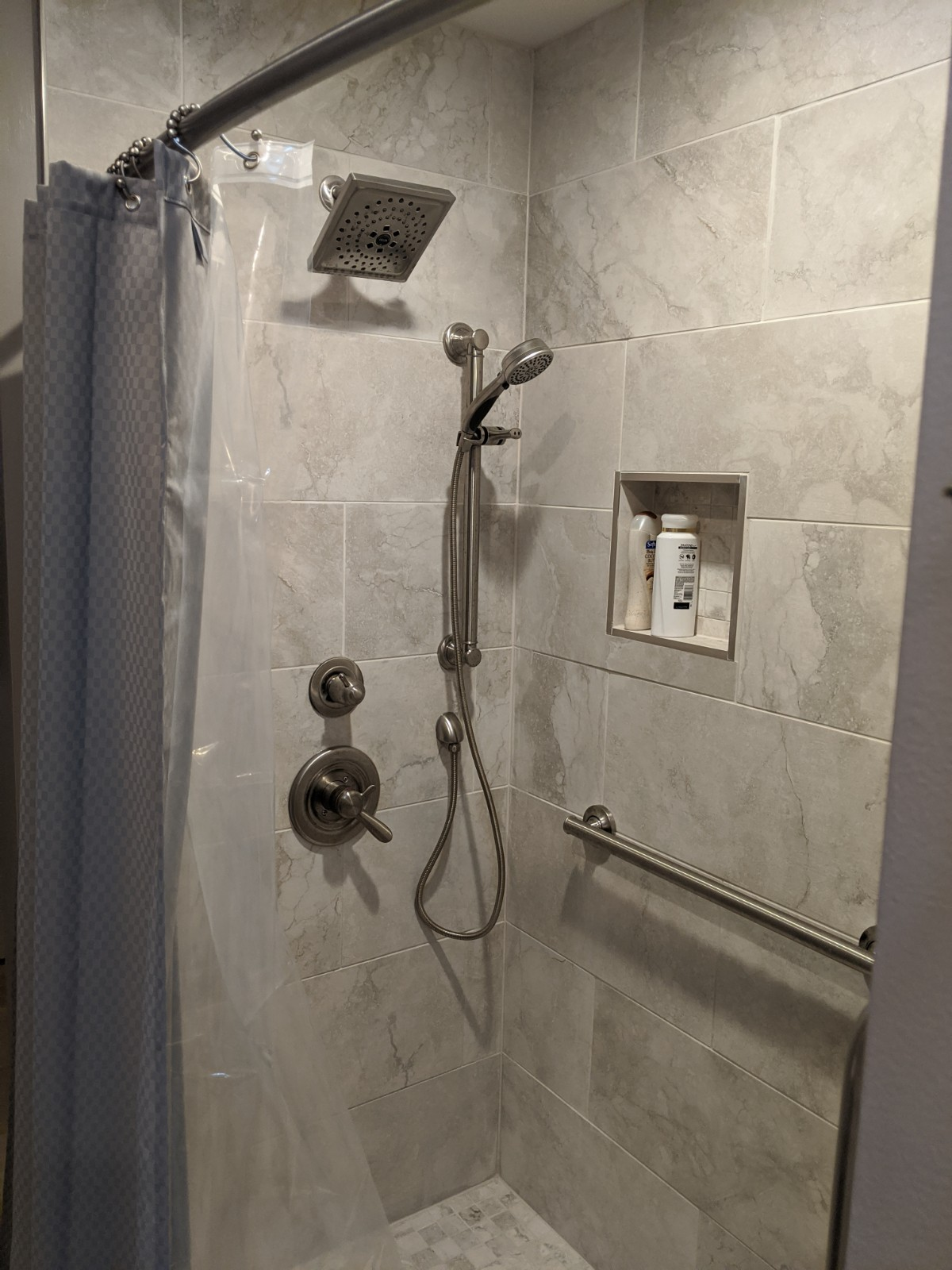 After shower picture, shower has marble style tile in a large format, new grab bars, handheld and shower head