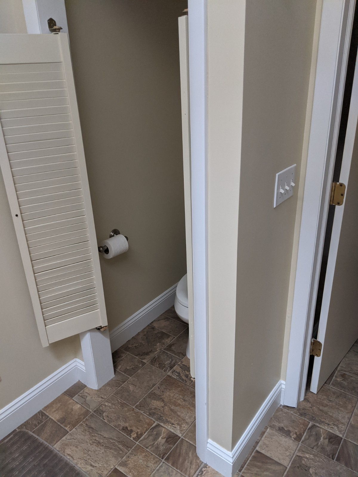 This pictures shows the outdated door on the water closet, as well as the brown 6 x 6 mixed tiles on the linoleum floor.