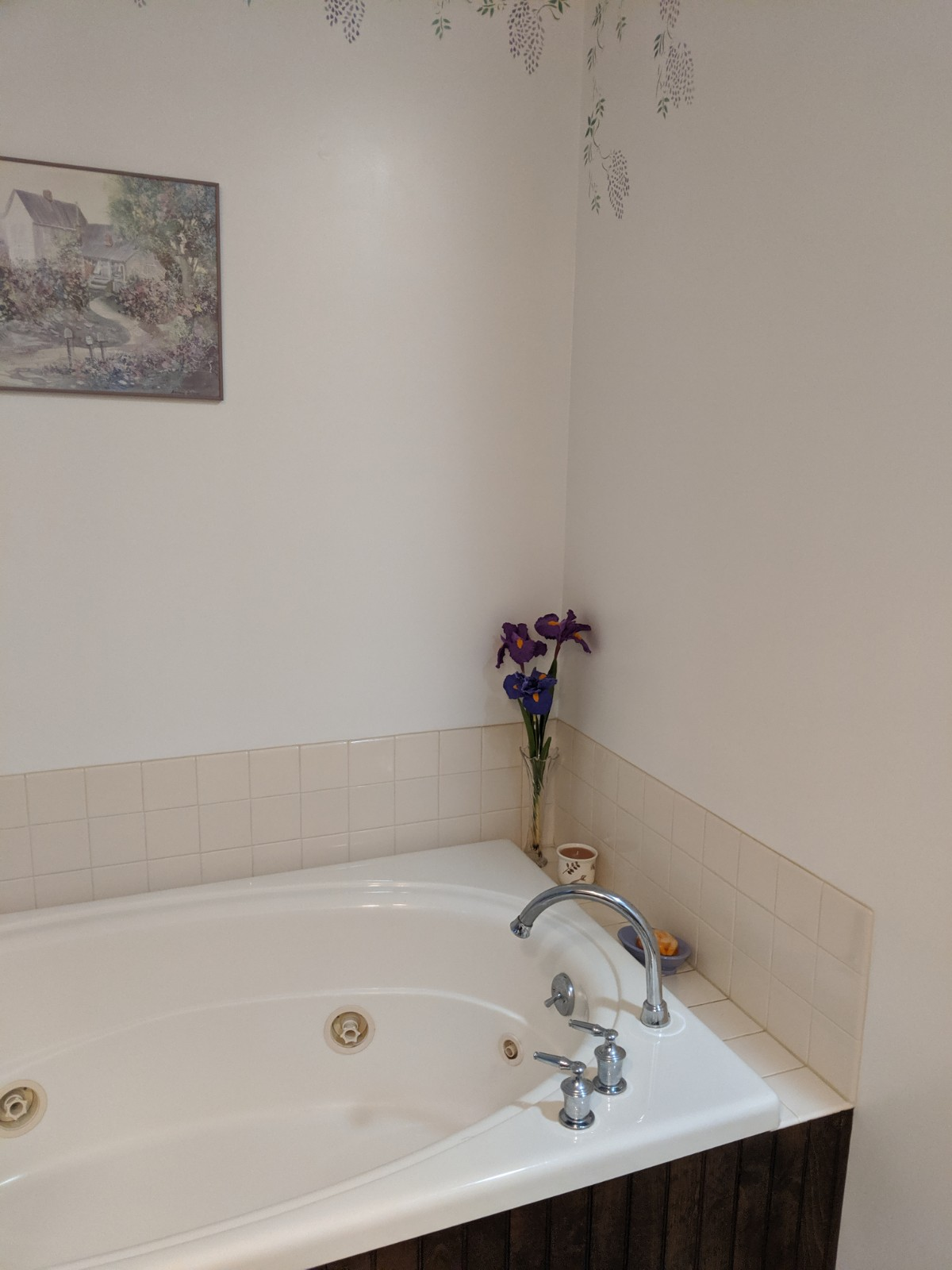 Tub area before the renovation, plan walls, tile and an outdated whirlpool tub