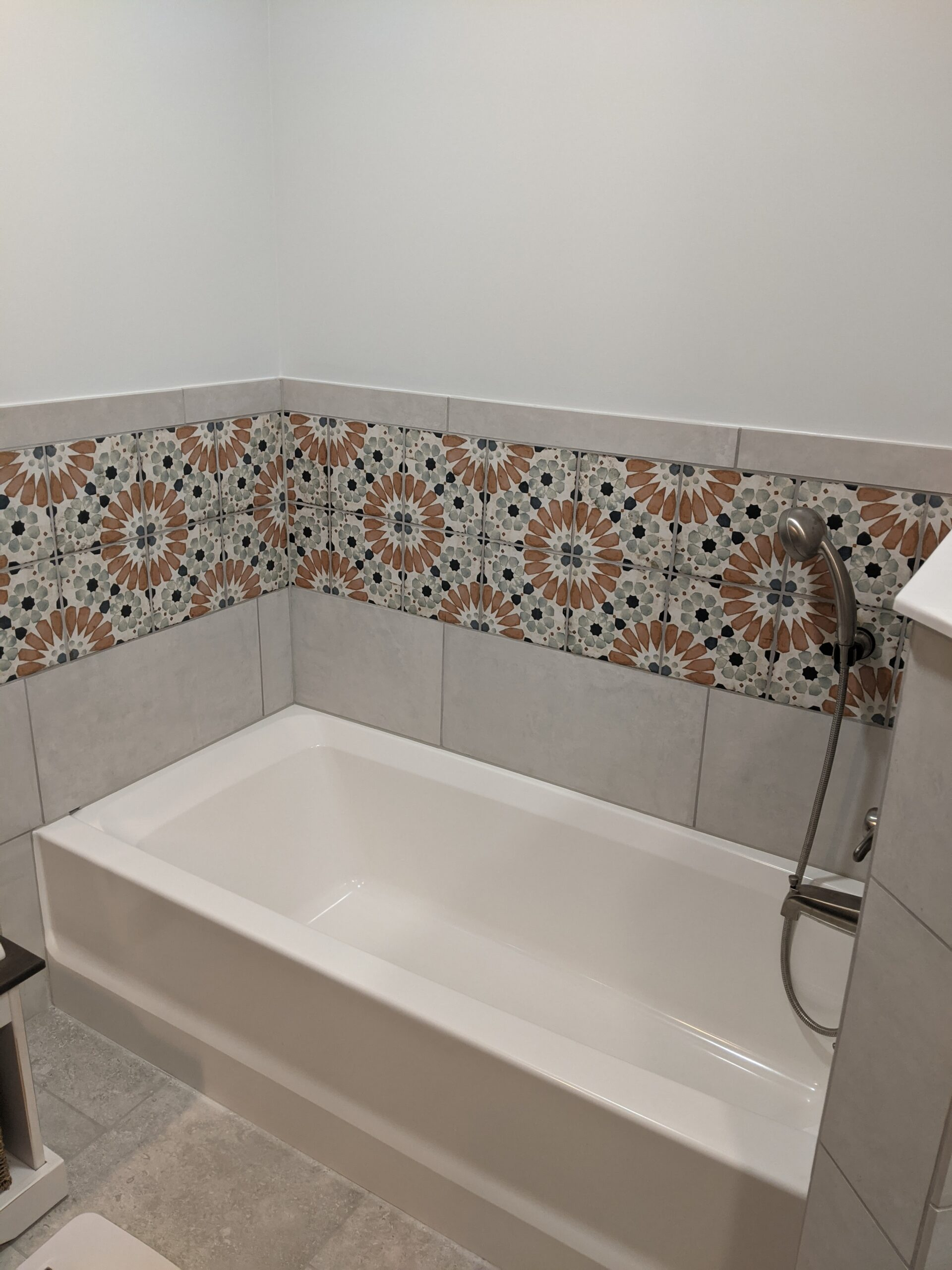 The tub area is now a standard tub with tile and decorative tile surrounding it.