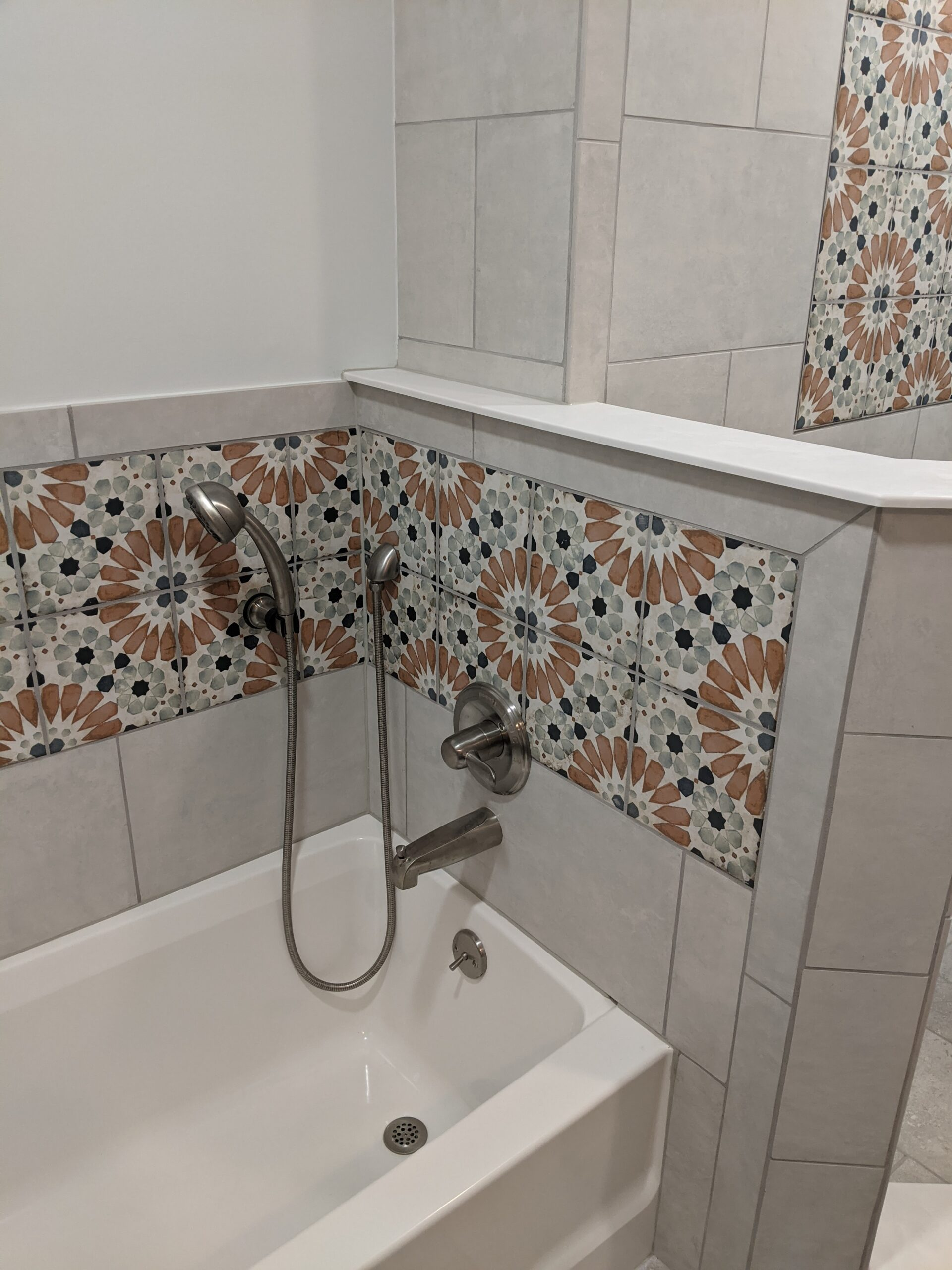 The tub area is now a standard tub with tile and decorative tile surrounding it with a hand held and new fixtures.
