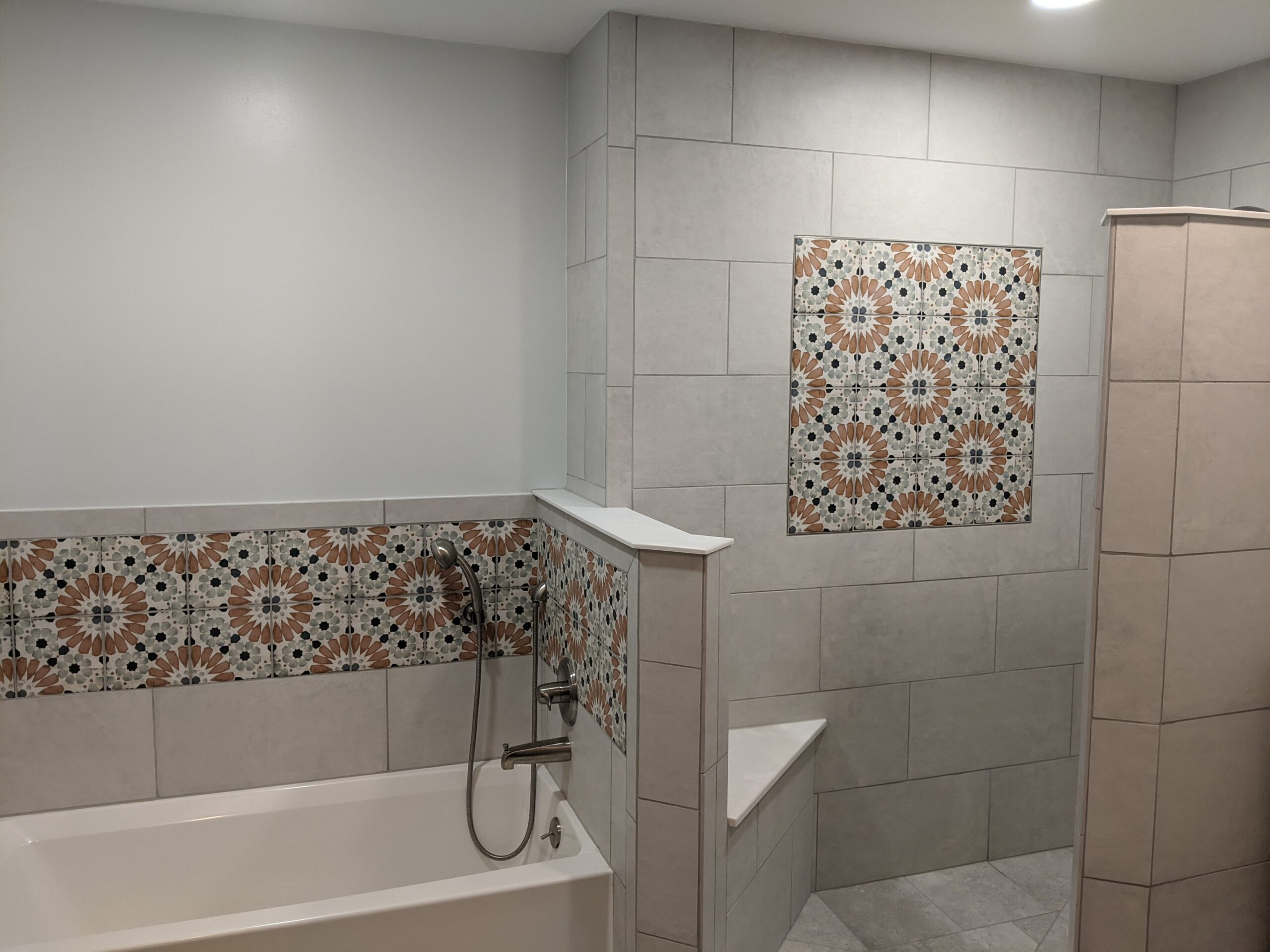 Tiled walls with decorative tile inserts allow the shower and tub areas to flow into eachother