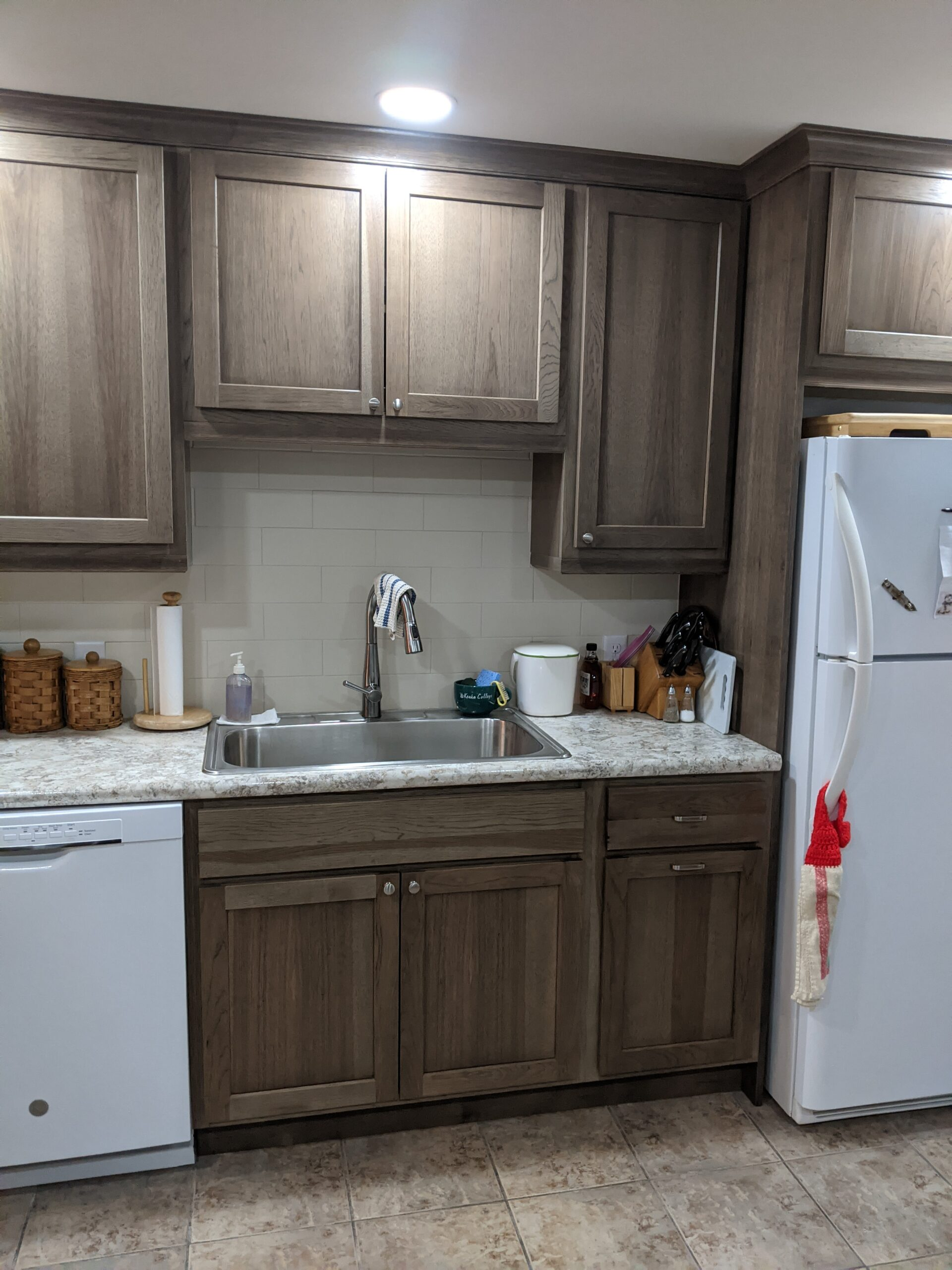 Sink area after renovations, with recessed lighting, soffits removed and Hickory cabinets in Morel finish