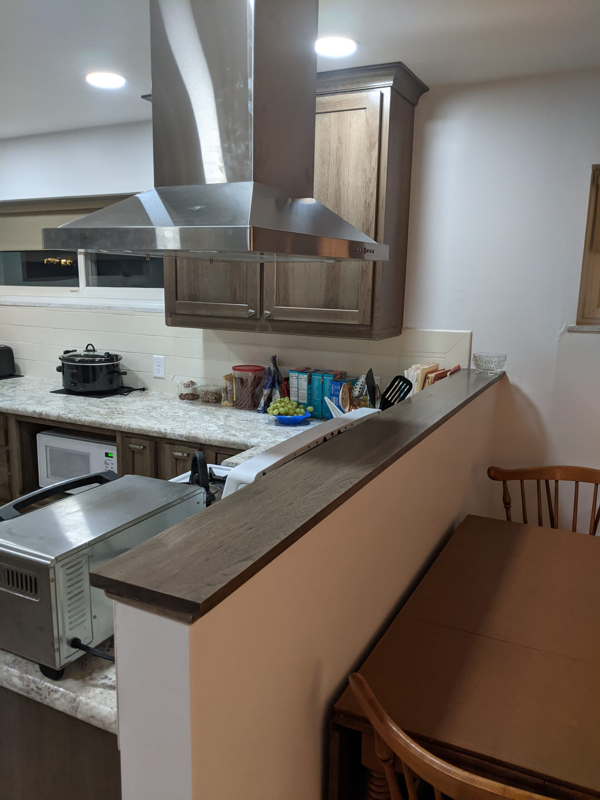Removing the upper cabinets and adding a chimney hood opens up the area looking into the kitchen